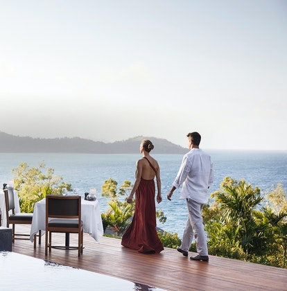 qualia Resort Couple Walking Through Outdoor Dinner Tables at Long Pavilion Restaurant with Whitsundays Views