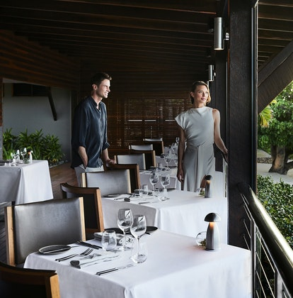 qualia Pebble Beach Restaurant With Man and Woman Standing By Tables Overlooking Beach