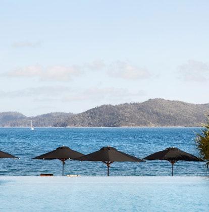 qualia Resort man swimming in Pebble Beach infinity pool with Whitsundays views