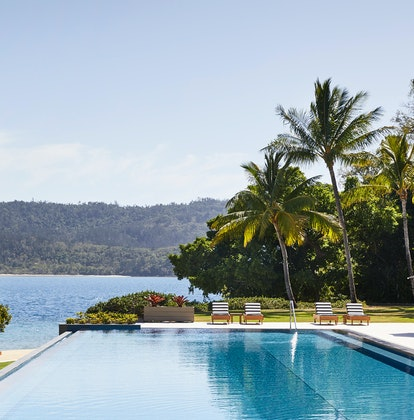 qualia Resort Pebble Beach infinity pool with palm trees, sun lounges and Whitsundays views