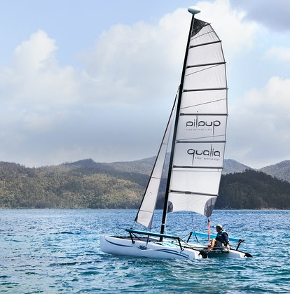 qualia Resort Pebble Beach catamaran with man sailing in the Whitsundays