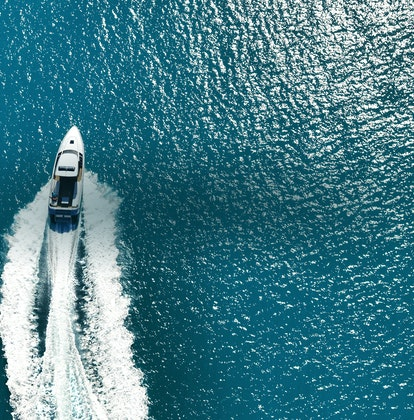 qualia Resort luxury experience activity with aerial view of boat charter and glittering sea