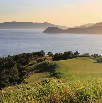 View of the Dent Island Golf Course hills with sunlight coming from across the Whitsundays