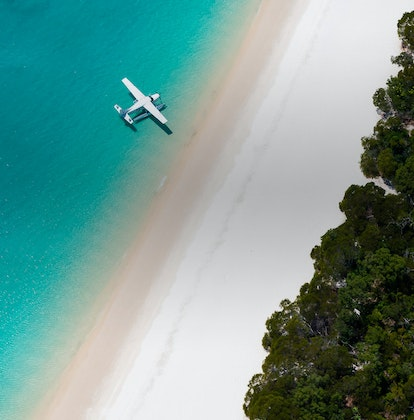Aerial view of luxury sea plane landing on waters as part of qualia's Whitehaven Beach Tour