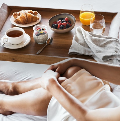 Woman sitting in qualia Windward Pavilion bed with breakfast tray including chia, berries and croissant
