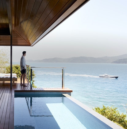 Man on qualia Windward Pavilion private deck with plunge pool looking out to luxury boat within view of the Whitsundays