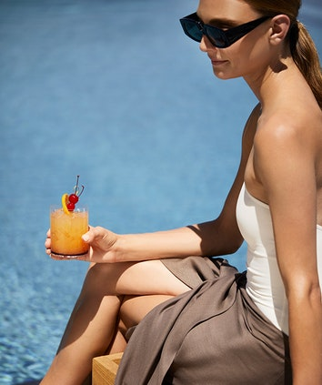 Woman in sunglasses holding fruit cocktail sitting by qualia resort pool in the Whitsundays