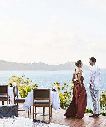 Couple standing by dinner table on Long Pavilion deck with views of the Whitsundays