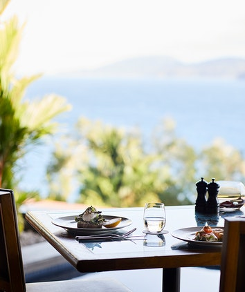 qualia Long Pavilion breakfast table with poached eggs and salad with Whitsundays views