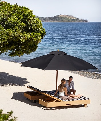 qualia Pebble Beach with man and woman sitting on striped beach lounges underneath umbrella