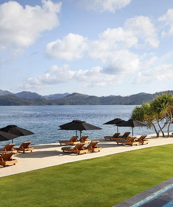 View of qualia Pebble Beach from resort pool lounges under umbrellas