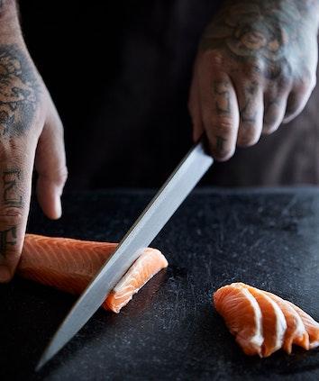 Chef hands slicing sashimi as part of Talk and Taste Sake and Sashimi experience at qualia's Long Pavilion restaurant
