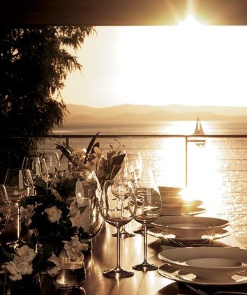 Close up of glasses, plates, and flowers on sunlit table and view of a boat on the Whitsundays in the horizon