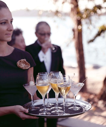 qualia female waiter carrying a tray of drinks at corporate retreat and out of focus man in the background having a drink