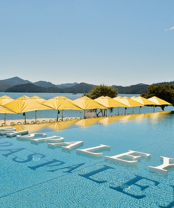 qualia infinity pool with letters 'Paspaley' floating in the water and yellow umbrellas and a view of qualia Pebble Beach