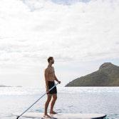 Man enjoying qualia resort experience of stand up paddle boarding at Catseye Beach