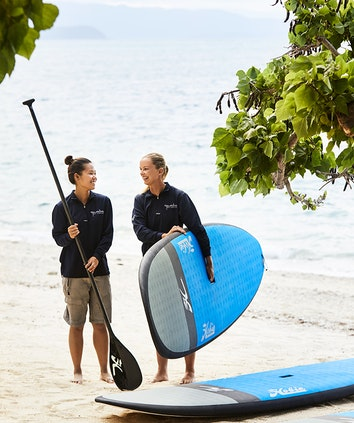 Two women part of the qualia beach sports team holding stand up paddle board equipment on the beach