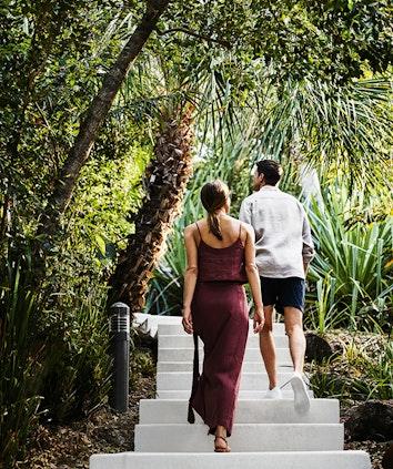A couple walks along a wooden boardwalk as part of qualia bushwalking activity