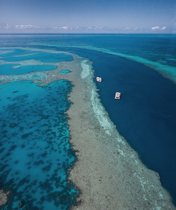 Aerial view from qualia scenic flight experience of boat and pontoon in Great Barrier Reef
