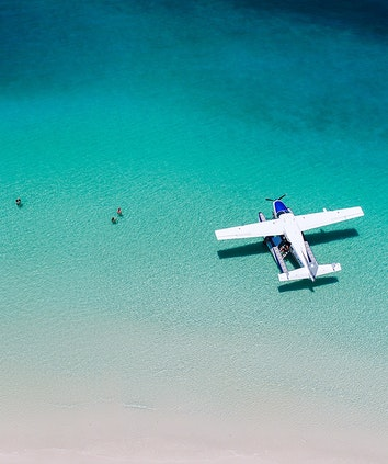 Couples enjoying the water at Whitehaven Beach near sea plane as part of qualia Scenic Flight Experience