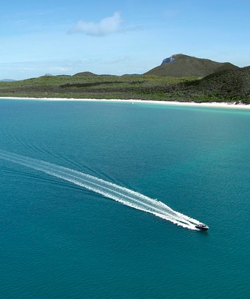 Aerial of boat leaving trail in water in front of Whitehaven Beach as part of qualia boating experience