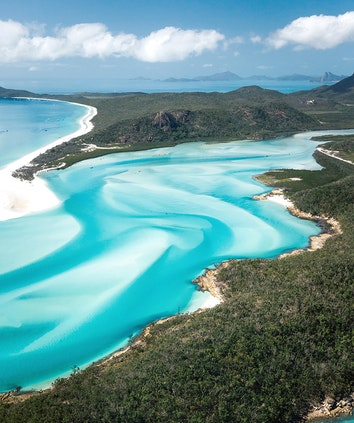 Aerial of swirling sand banks and turquoise water at Whitehaven Beach near qualia resort