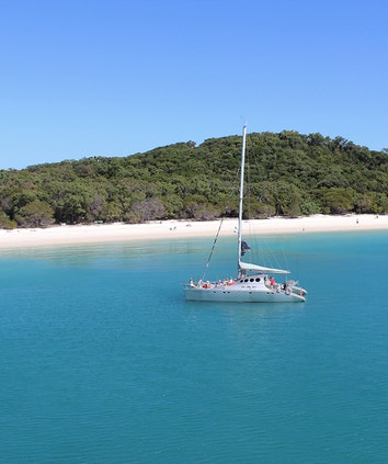 Sailors on Ricochet luxury catamaran in front of beach as part of qualia luxury experience