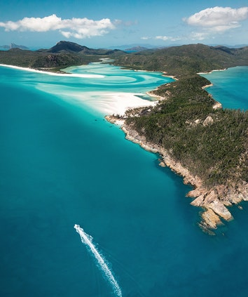 Aerial of boat leaving trail in water in front of Whitehaven Beach as part of qualia scenic flight experience