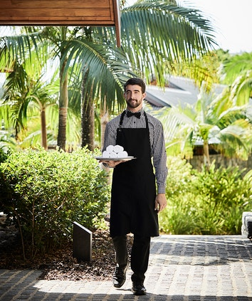 qualia resort waiter bringing tray of face towels through garden grounds