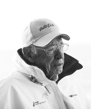 Black and white portrait of Bob Oatley wearing glasses and baseball cap with Wild Oats embroidered on it