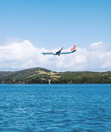 Qantas plane flying low above the water by Hamilton Island