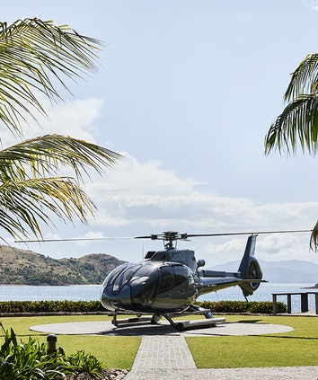 Helicopter landed at private helipad surrounded by gardens and Whitsunday views