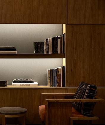 Armchair and bookshelf in qualia resort Long Pavilion library with wooden shelving