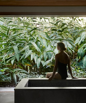 Woman sitting on edge of bathtub in spa qualia treatment room looking at lush foliage outside window