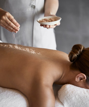 Salt scrub being sprinkled onto woman's back in spa qualia treatment room by spa therapist