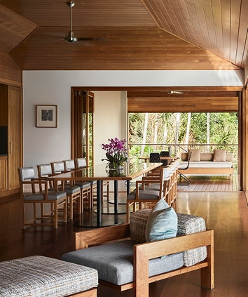 Armchair, ottoman, and dining table with ten chairs inside qualia resort's Beach House