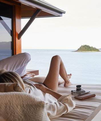 Couple laying next to camera and notebook in a day bed looking out at Whitsundays views from qualia resort pavilion