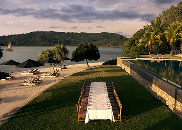 Aerial view of long table with white cloth in the grass and qualia infinity pool to the right and Pebble Beach to the left