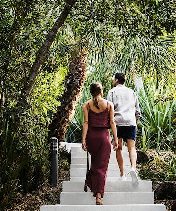 Couple walking along wooden boardwalk amongst tropical bush landscaping at qualia resort in Whitsundays