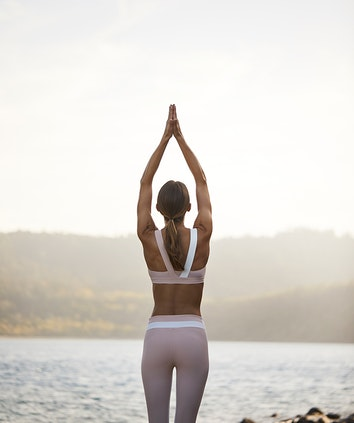 Woman in active wear with hands raised in prayer facing the Whitsunday waters at qualia resort