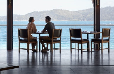 Couple sitting at Pebble Beach restaurant table for lunch with views of Whitsundays