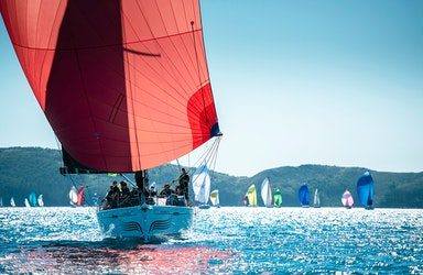 Sailing fleet passage in the turquoise waters of the Whitsundays at Hamilton Island Race Week