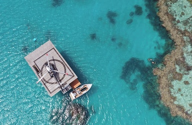 Aerial wide view of pontoon and jet ski during the qualia experience of Journey to the Heart