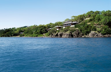 exterior view of qualia resort and surrounding trees from the calm waters of the Whitsundays