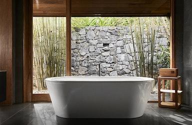 View of white bathtub and stone wall at qualia Beach House bathroom