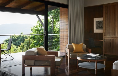 Leeward Pavilion lounge open doors towards private terrace with view of trees and the Whitsundays