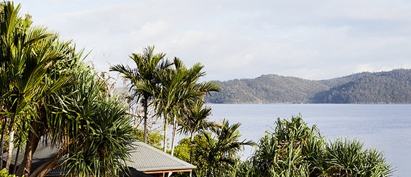 qualia resort view of covered Beach House deck with sun lounges and Whitsundays views surrounded by palm trees
