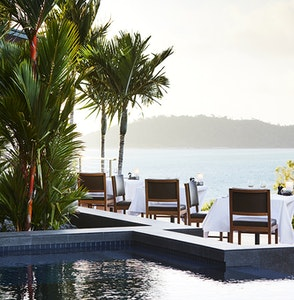 View of poolside qualia resort restaurant tables and chairs surrounded by palm trees and views of the Whitsundays