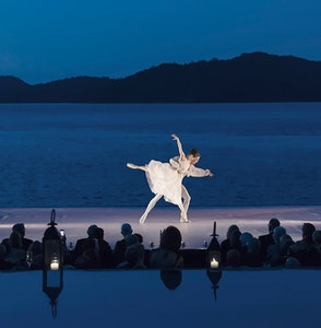 Female and male ballet dancers performing in front of an audience at qualia resort and Whitsundays in background