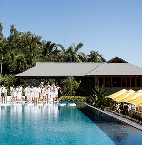View of group people dressed in white and large lunch table under yellow umbrellas from across qualia inifinity pool